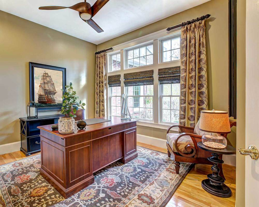 The office has a cherry desk, custom draperies and a hand knotted area rug in brown, terracotta and blue.