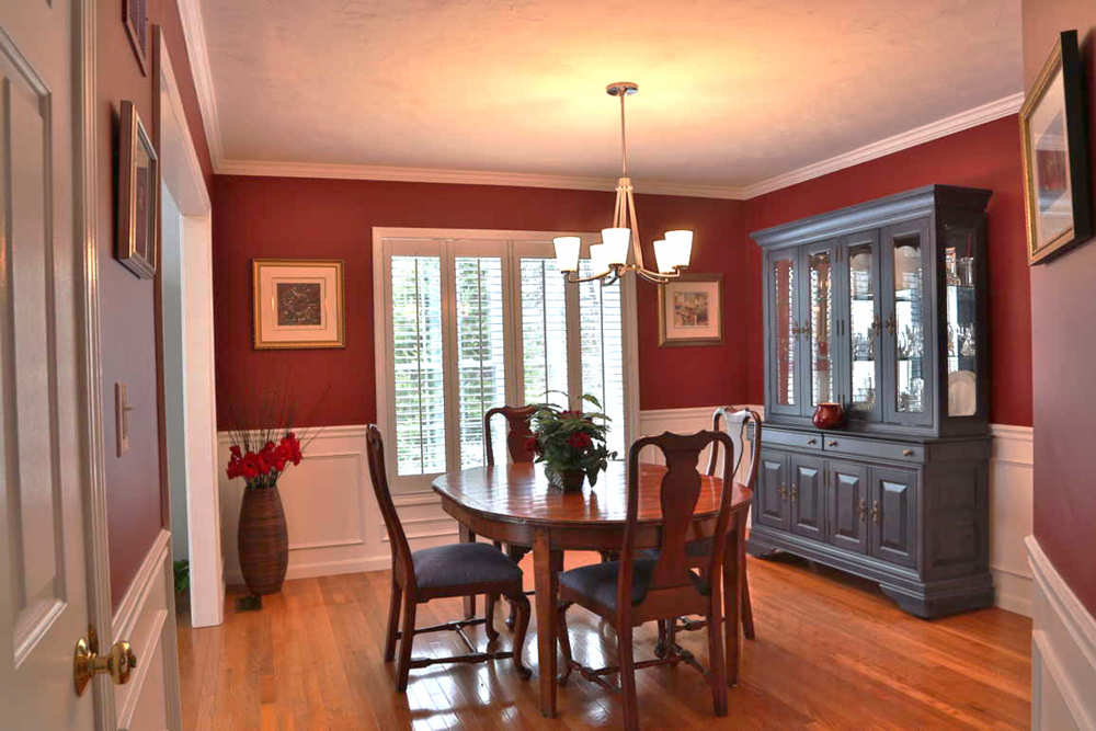 The white wainscotting and deep red walls of this luxurious diningroom makes a bold statement and conveys luxury. The paint color is Benjamin Moore 2080-10 Raspberry Truffle. The room was overcrowded so much of the existing furniture was reused in different rooms.