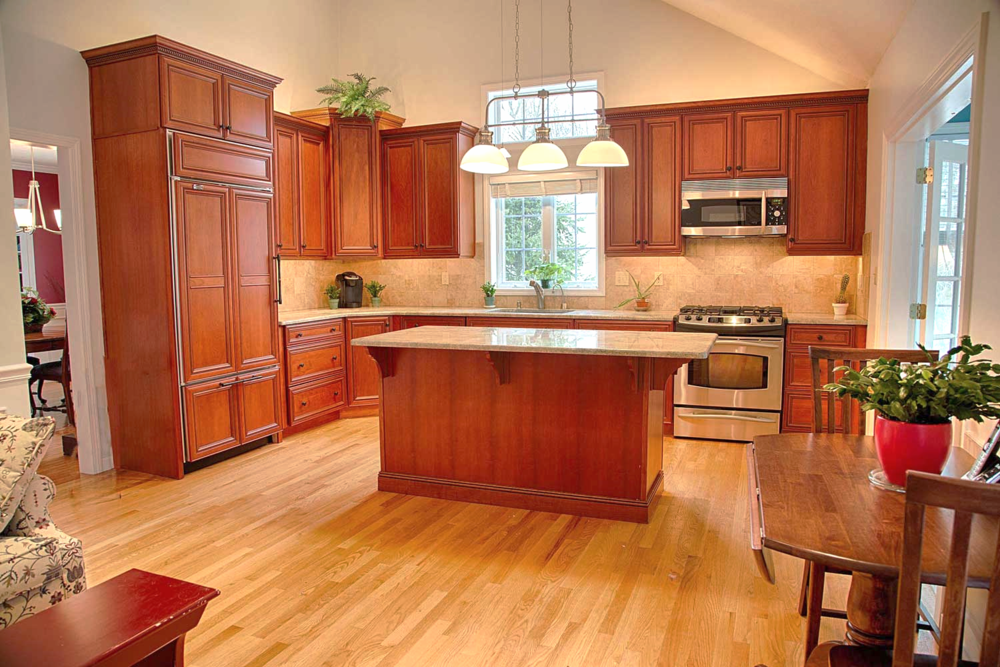 The exquisite kitchen has a timeless design and is easily maintained. The wall color is Sherwin Williams Silverpointe, allowing for the warm cherry kitchen cabinets to be noticed. The countertop is granite. The cabinets were designed to create space for the removal of clutter.