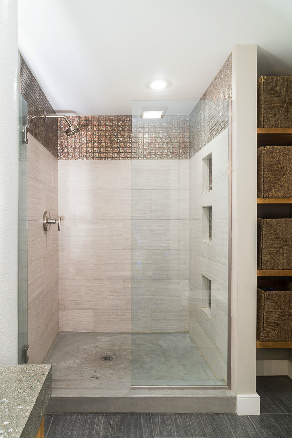 "The shower door is a½"" glass enclosure with brushed nickel frame and handle and the shower walls are Stratos silver with dove gray grout."