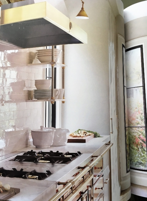 Polished backsplash tile, honed countertop, iron-look window, wall sconce lighting and mixing of metals on shelf brackets