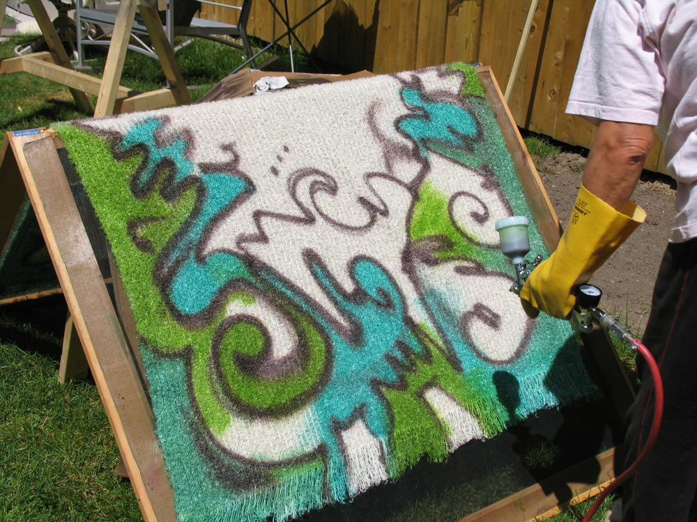 Dar uses an airbrush gun filled with dye to spray paint in repeated layers in order to build enough intensity of colour.
