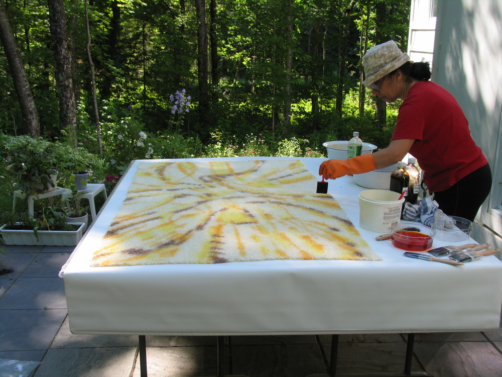 Dar talks with her hands too, as she paints hot dye onto the white mohair cloth.