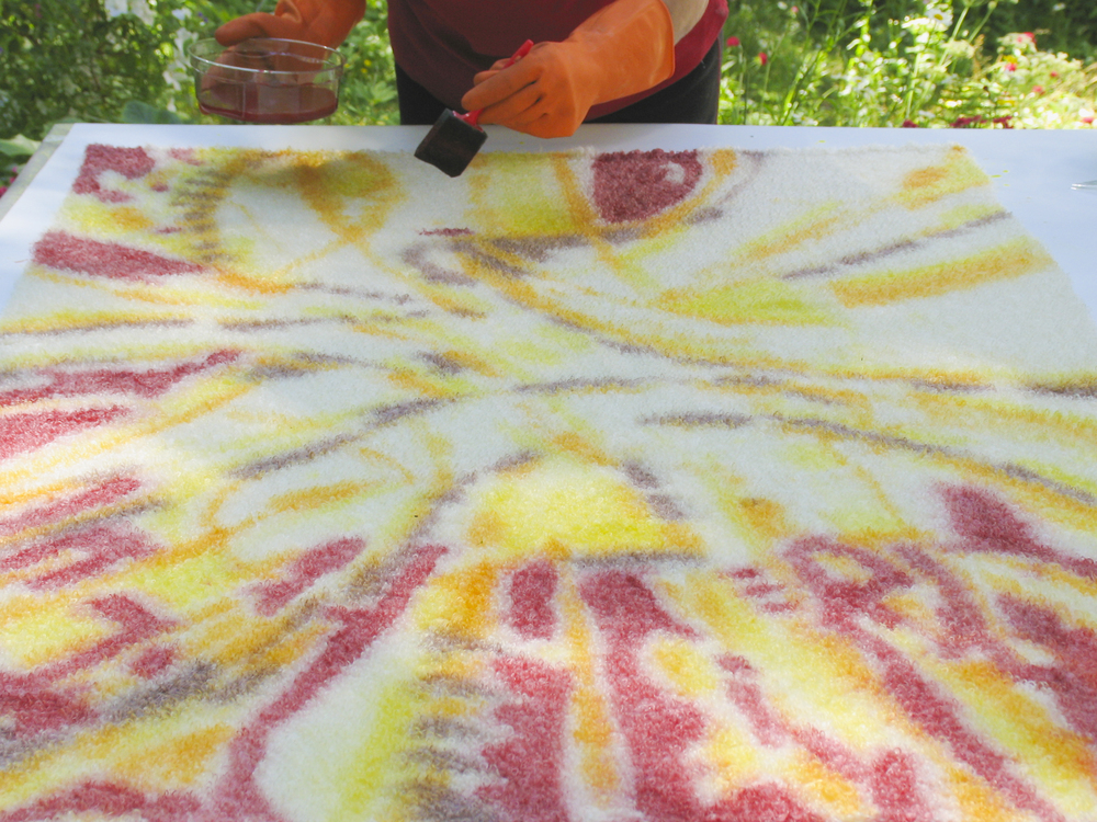 Dar hand painting first layers onto a white throw.