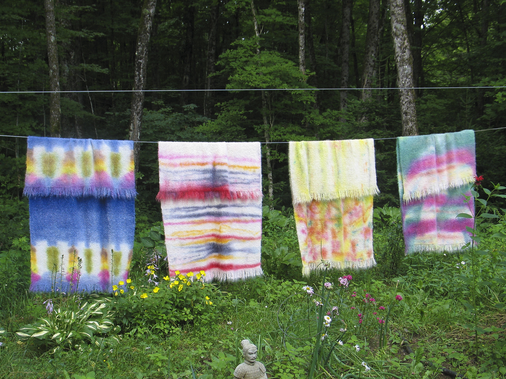 Painted throws hanging to dry on the line.