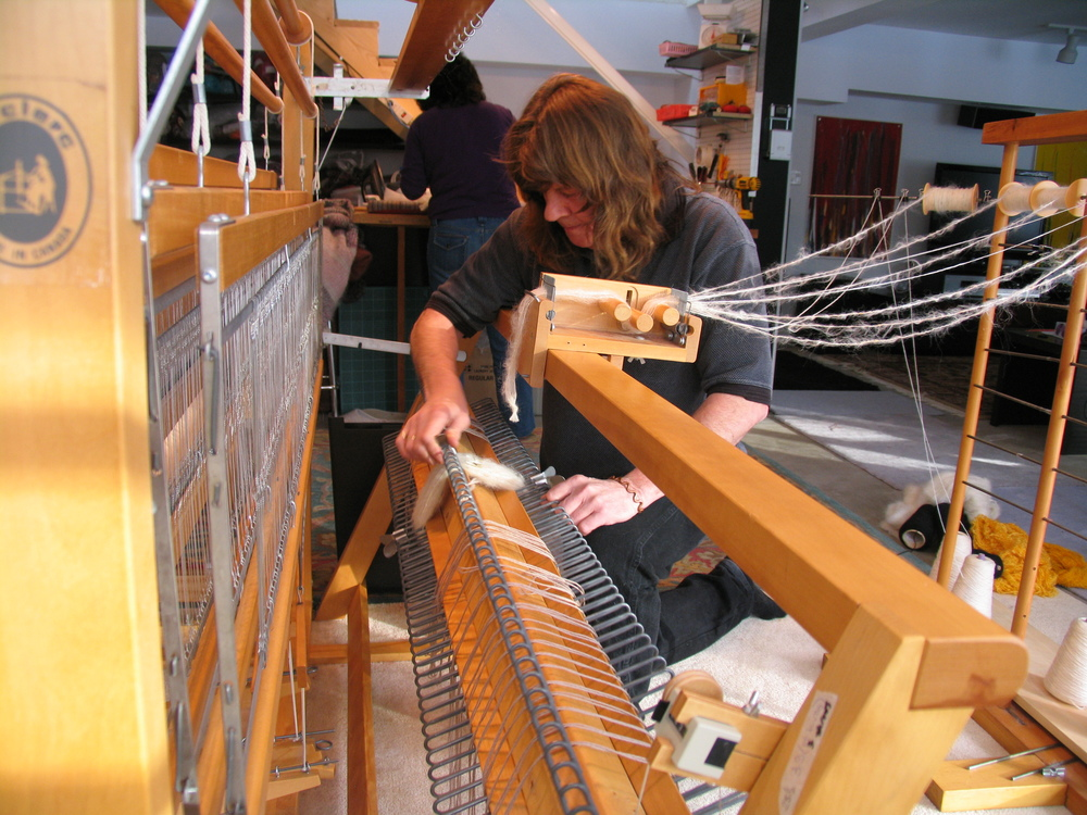 Charly loading one of our looms for a new series of throws in our Haliburton studio.
