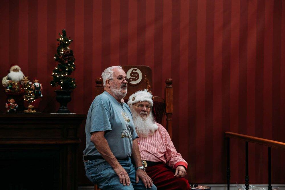 äldre man sitter i jultomtens knä i North Pole Alaska