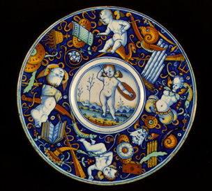 Plate with border of putti and trophies amid grotesques, tin-glazed earthenware (maiolica), 23.2 cm (9 1/8 in.)