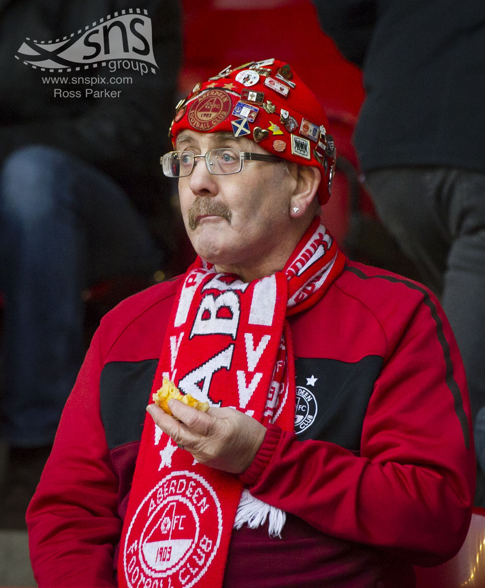An Aberdeen fan awaits kick off as his team face Dundee United at Pittodrie.