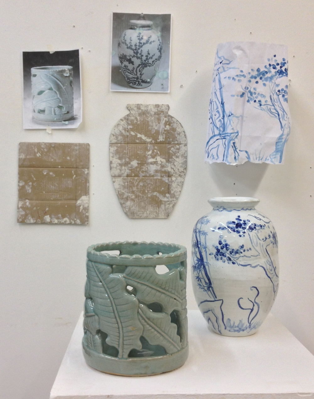 Here a student scaled up what is normally a small celadon brush holder, along with her cobalt pot.  On the wall behind the pots are the drawings and templates she used to help understand and produce the pots.