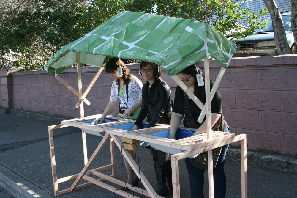 """Gimme Shelter"" was a collaborative project where groups of three students were asked to brainstorm and construct a large ""shelter,"" that would actually or metaphorically protect the user from a perceived danger.  Besides teaching the students planning, space and scale, they were also asked to consider the importance of site.  Here, three students show an urban bus shelter that allows users to temporarily consider other natural settings or locations as a reparative to the assaults of urban living.  Wood, three different soundtracks, headphones, audio playback, plastic sheeting, found natural materials."