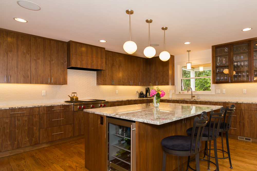 Kitchen detail with custom walnut cabinets, granite countertops, and handmade glass pendants over large island.
