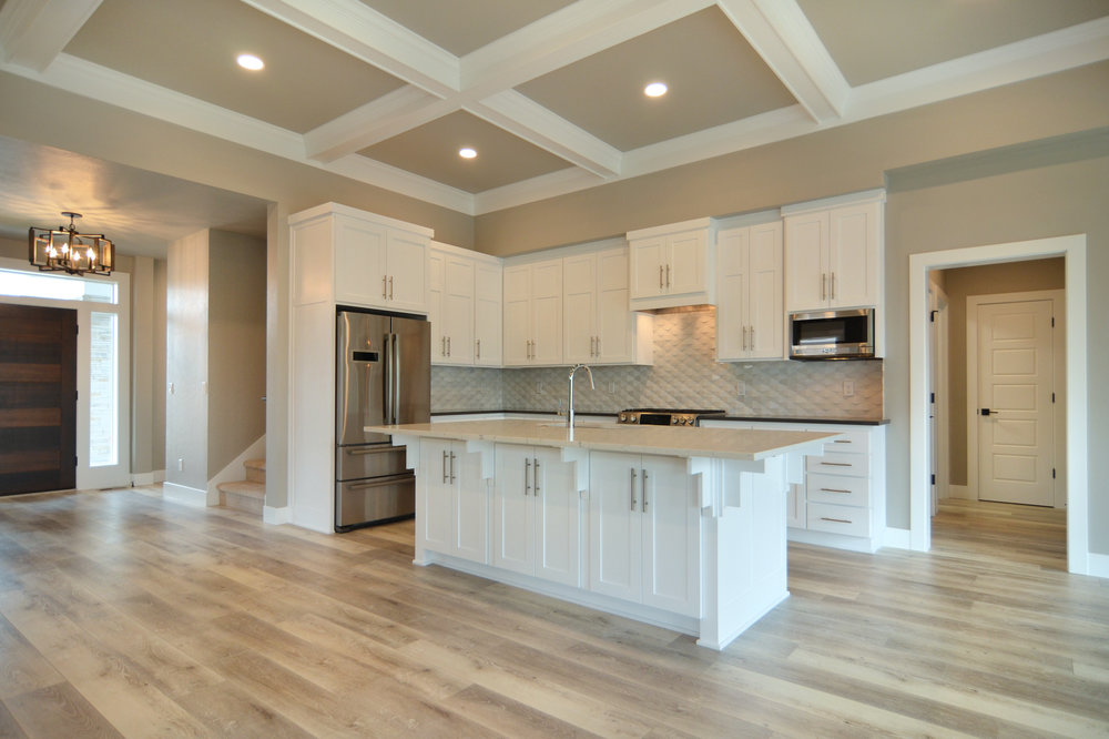 Custom Chef's Kitchen with coffered ceiling, granite counter tops and tiled backsplash.