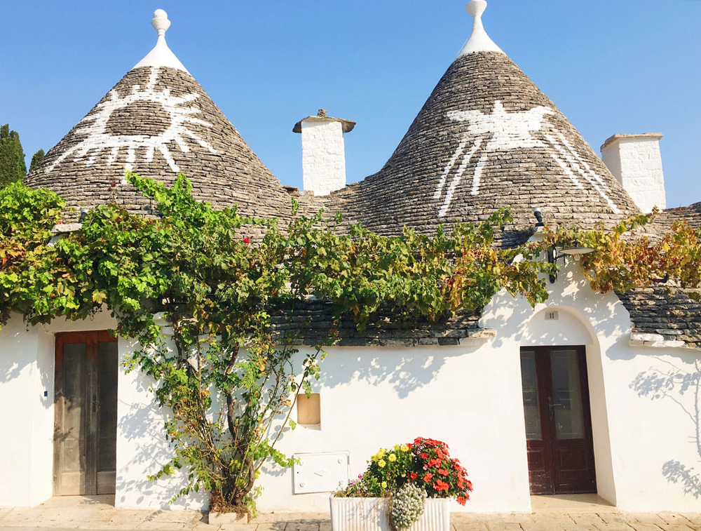 Trulli houses with signs in Alberobello, Italy in Puglia | freckleandfair.com