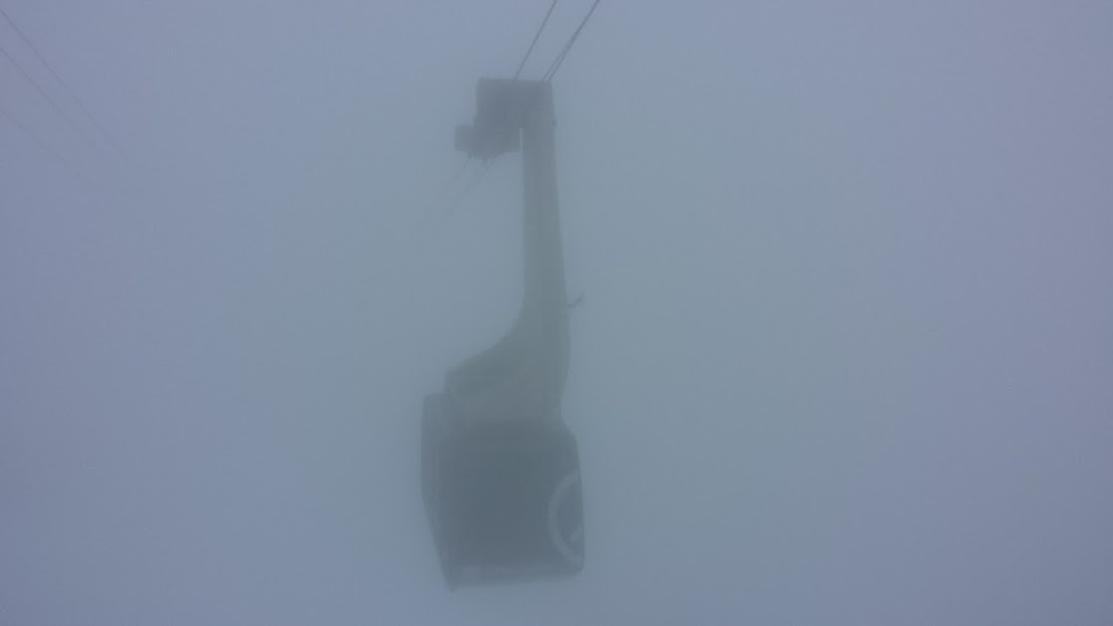 The cable car swimming out of the fog and into the station.