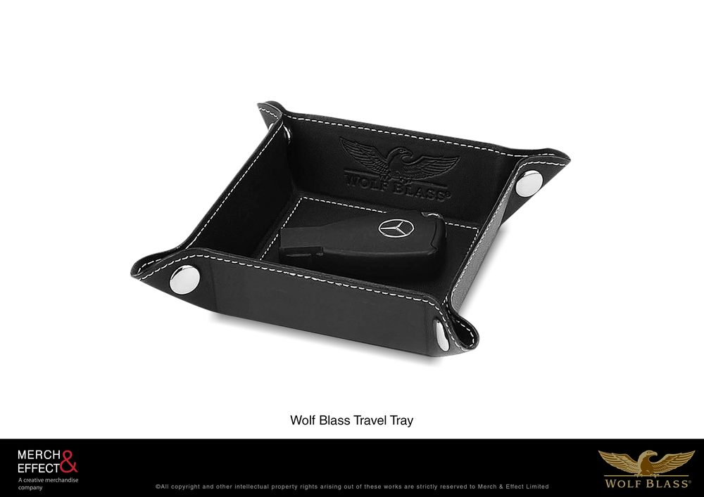 Travel in style with this exclusive Wolf Blass Travel Tray. Made as a GWP for Treasury Wine Estates' Wolf Blass Gold Label Wines, this travel tray comes in a classic black box with gold logo of Wolf Blass, while the item itself is debossed with the brand logo and finished with refined white stitching. It can hold your portable car charger, keys and other items as you travel alone or with your loved ones.   It has metal snap buttons on its four corners to hold its form when in use