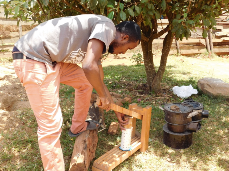 Sungani molds a single briquette with their homemade press. This is their primary form of production until they raise enough funds to purchase an automated press.