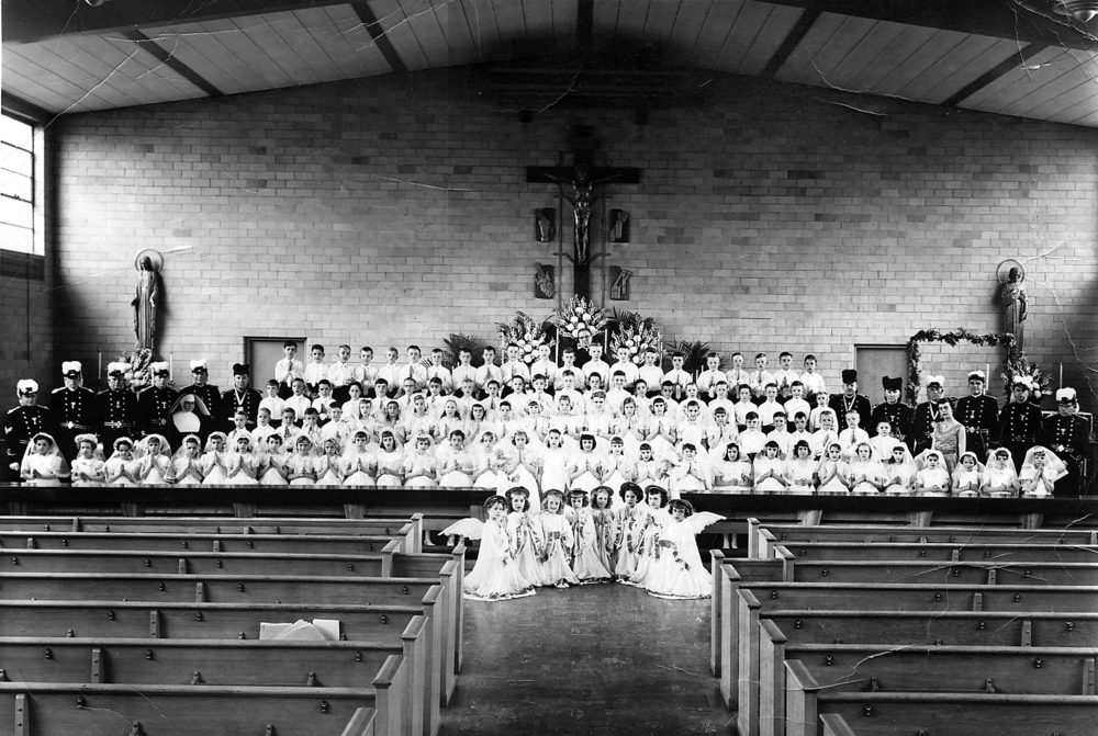 First Communion class in the interior of first permanent church (now Lux Hall/Gym)