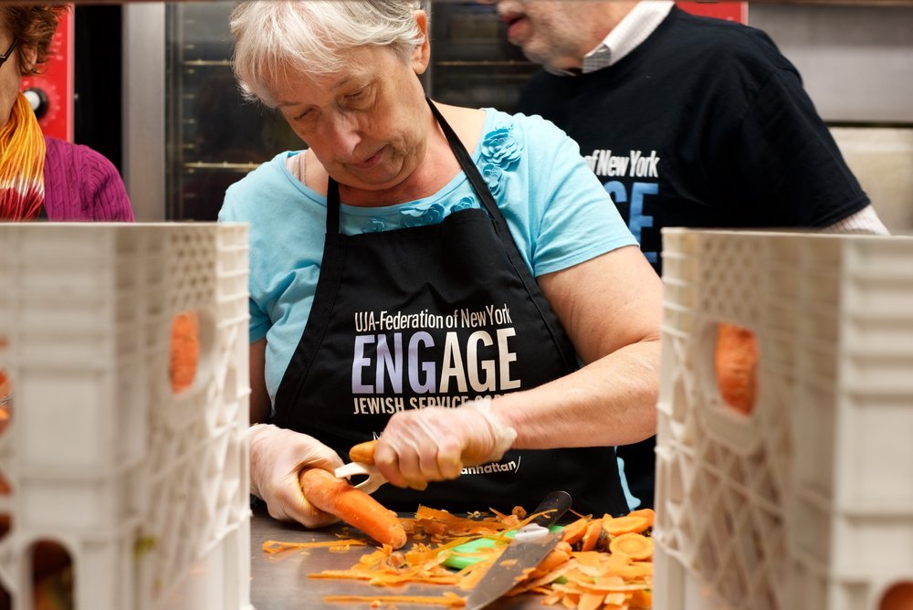 Joan Kaplan, Brooklyn volunteer, peeling carrots at Masbia food pantry