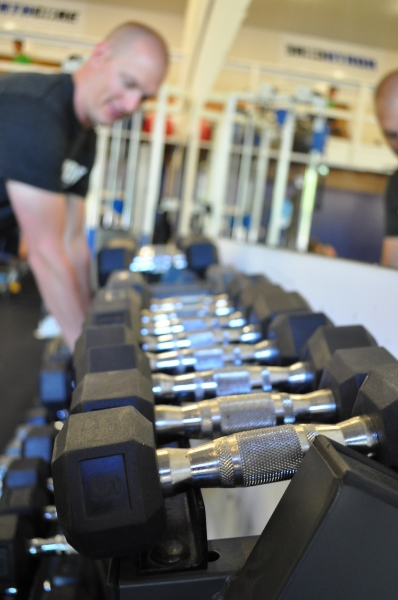 Jeff pulling dumbbells off of a rack at Northcore