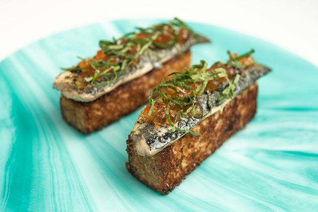 Seared Portuguese sardines on brioche, smoked steelhead trout caviar, black garlic, and shiso