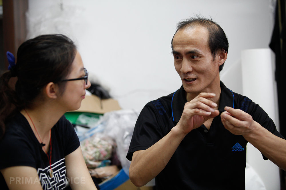 Interpreter Zhu Lei listens to  Chen  during an interview in 2014. Photo courtesy of Daniel Huang.