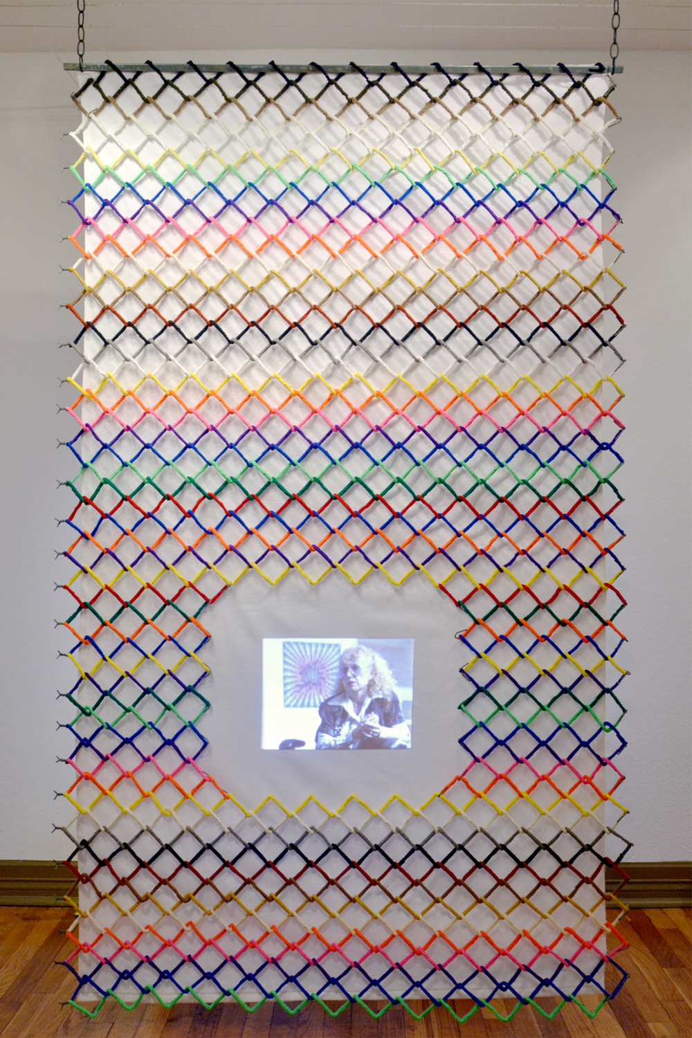 Let Me In Let Me Out Acrylic yarn, chain-link fence, cotton flannel and digital video projection with sound 80 x 48 x 2 in.