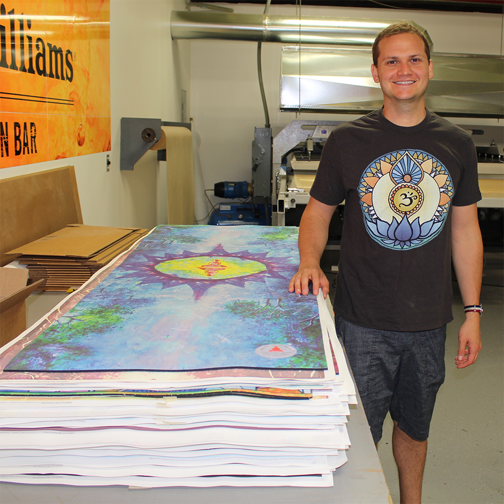 CEO & CoFounder of Sankalpa Yoga, Josh Nickell, stands next to a batch of our first ever printed mats.