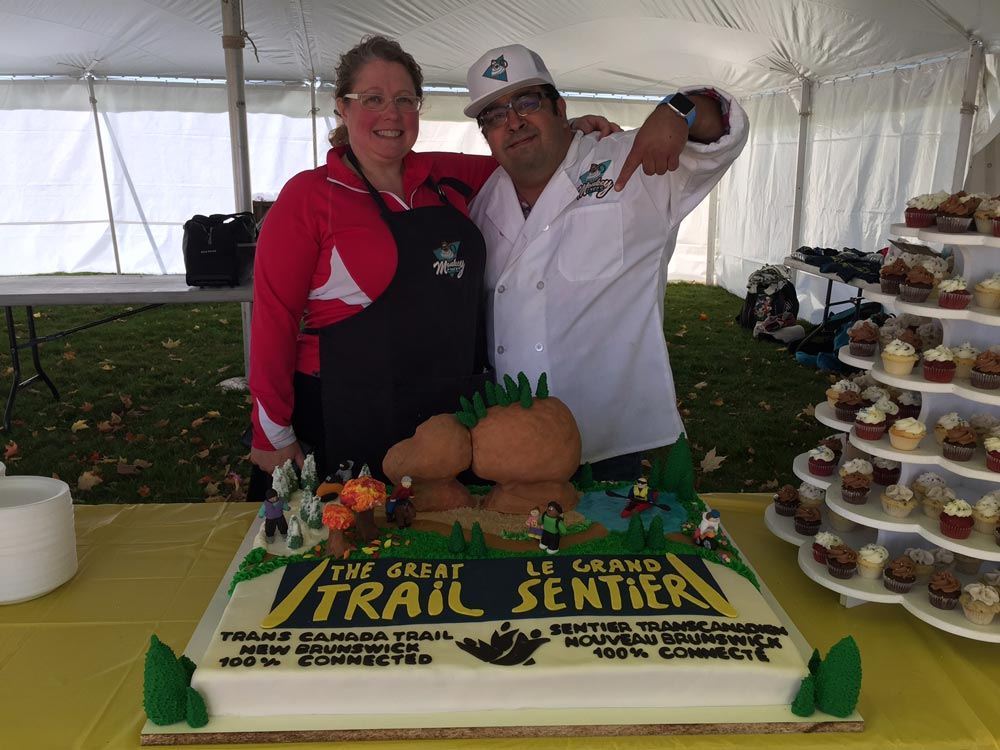 Monkeycakes' Jonathan and Natalie Ramirez posing with The Great Trail cake