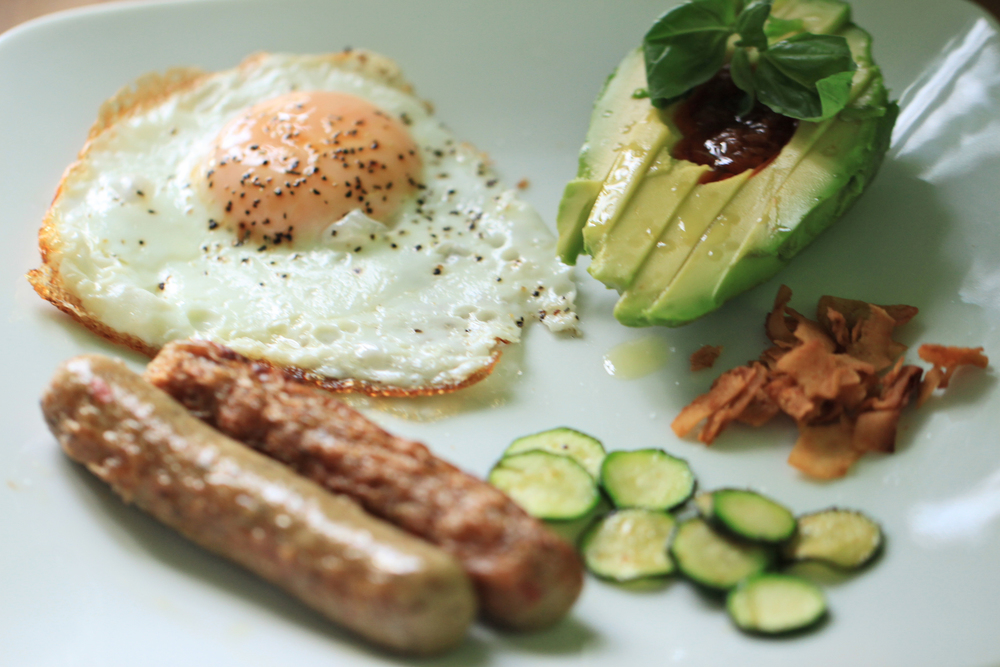 """This was the breakfast I prepared for my friend Michael the other day: Fried egg, avocado with a little tomato achaar and basil, chicken sausage, sauteed zucchini and some crispy coconut """"bacon"""" flakes by YEAH DAWG."""