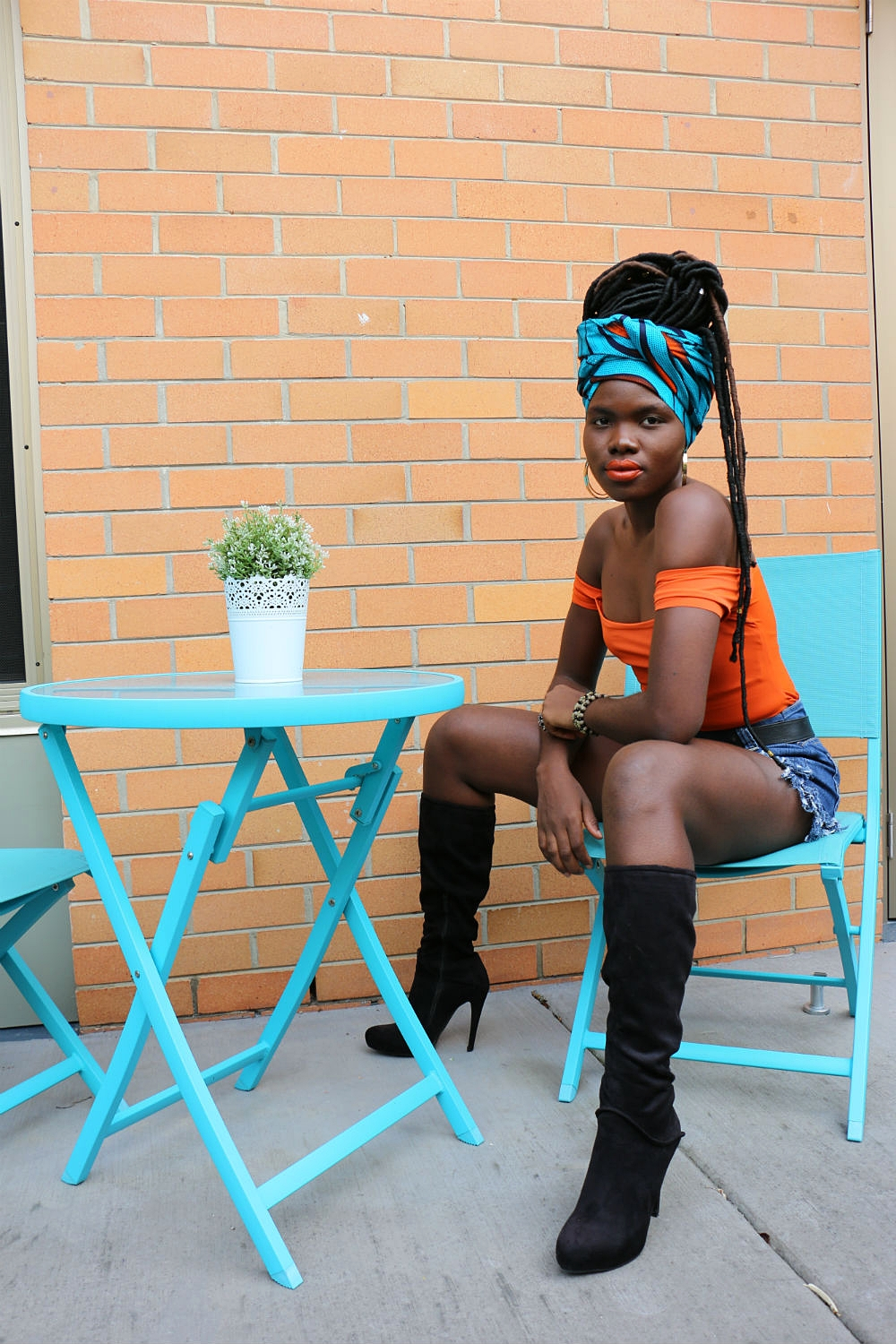 In line with our colour palette and mood board, Mariama opted for a pair of knee high black boots (edgy and chic), a denim shorts that she had recycled from a jeans and an off-the-shoulder boldly coloured orange bodysuit.