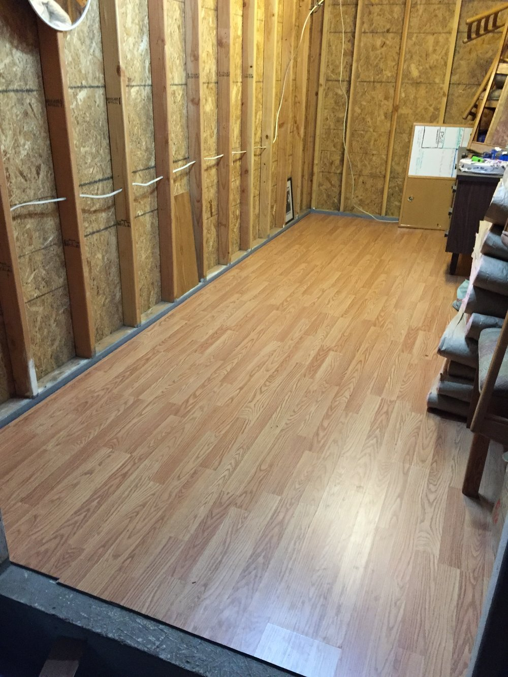 After fake wood flooring laminate was added, the insulation & drywall still needed to go up.