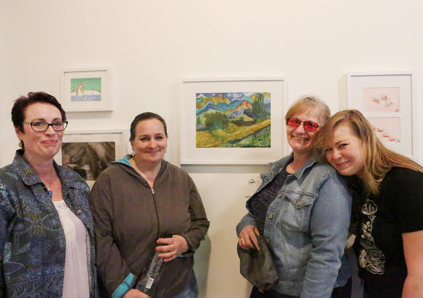 Tracy Lester standing beside her first exhibited painting with her sisters and niece.