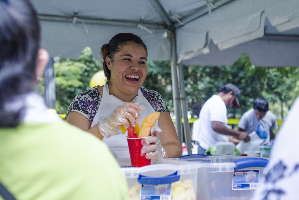 "Underneath one tent in Krutch Park, Jessica Chavez prepares a ""Vaso de Frutas"" of pineapple, watermelon, mango, cantaloupe, a squeeze of lime and a dash of chili powder for a long line of customers."
