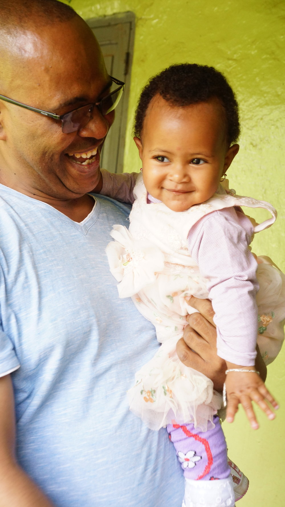 Sintayu M. with her new father. She has found a family with older siblings who absolutely dote on her and treat her like a little princess!
