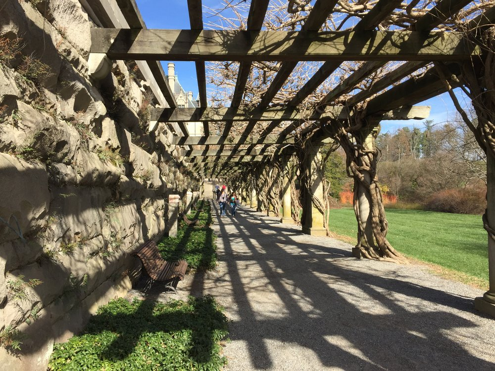 The grounds feature a long pergola adjacent to the house.
