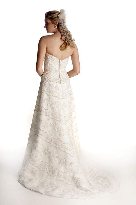 Strapless, organza, gold embroidery creates floral garlands through-out body of the princess waist gown. Matching veil.