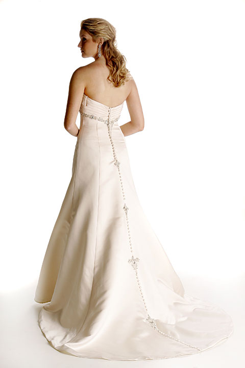 Blush Italian satin is pleated in the bustline which is underscored with rich beading. The chapel train is centered with covered buttons and graduated clusters of beading that form a magnificent bustle for the reception.