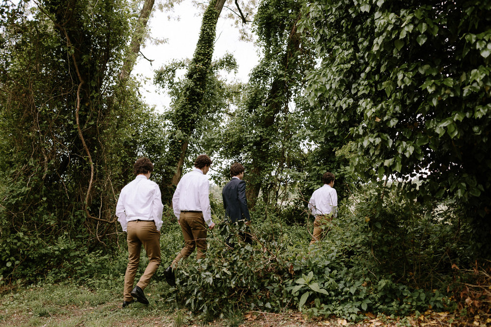 Groomsmen walking through woods