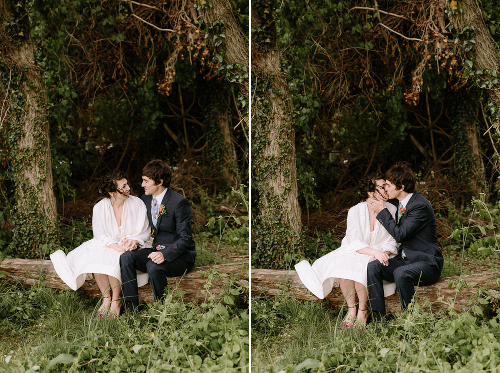 Bride and groom sitting on fallen tree kissing