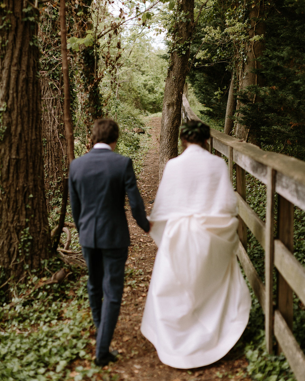 Bride and groom walking along forest path