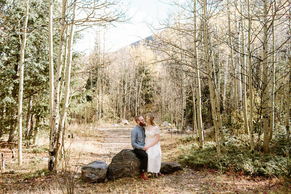 Guanella Pass bride and groom sitting on a rock