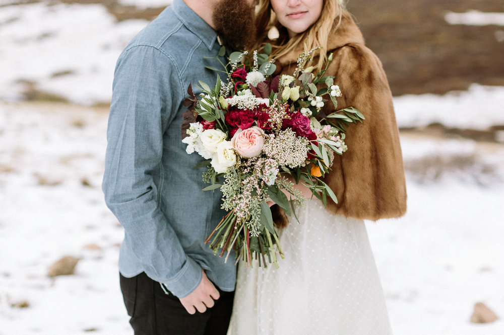 Bride and groom on mountain with flowers