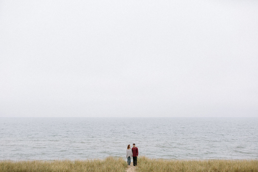 Girl and guy standing on beach beside Lake Michigan