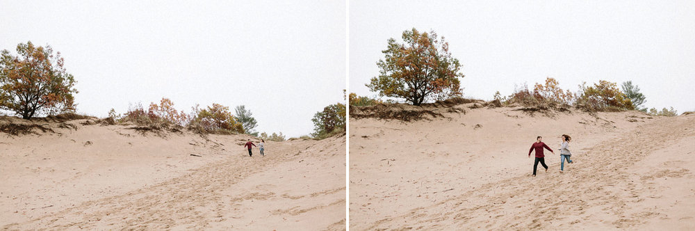 Couple running down dunes