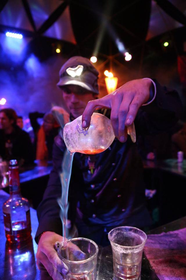 One of Incendia's bartenders pours a flaming shot as onlookers marvel.