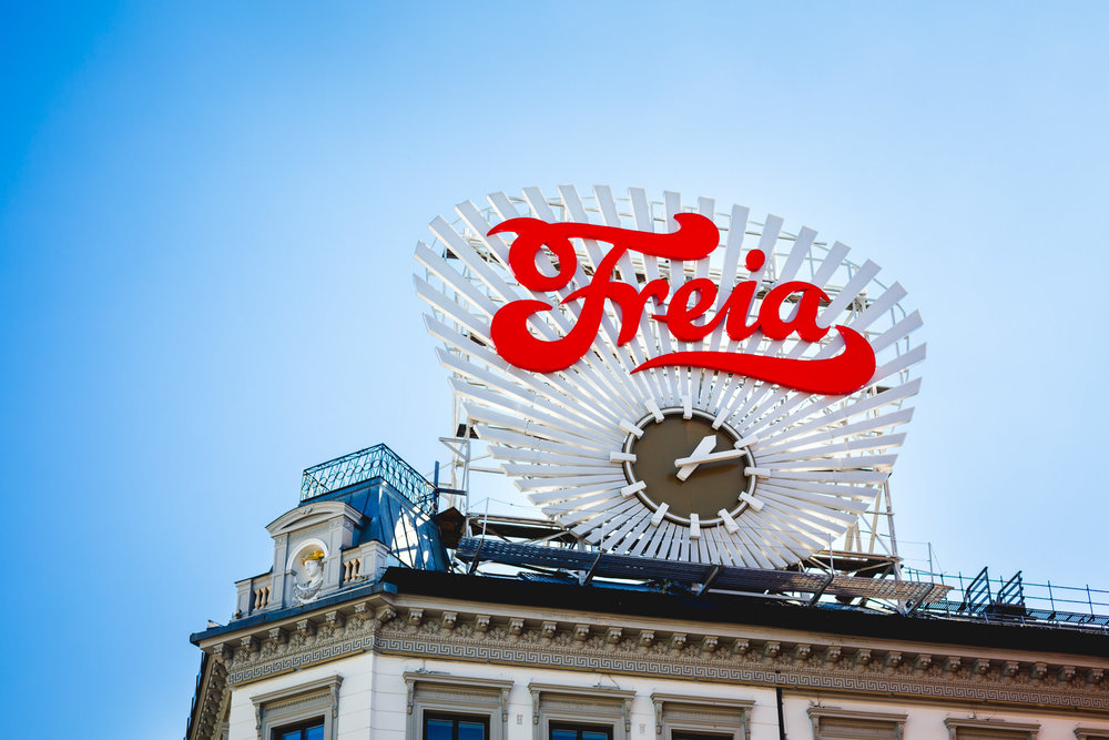 Freia (a popular brand of chocolate in Norway) on show on a large clock. This is visible at a distance from The Royal Palace as a road runs straight down to it.