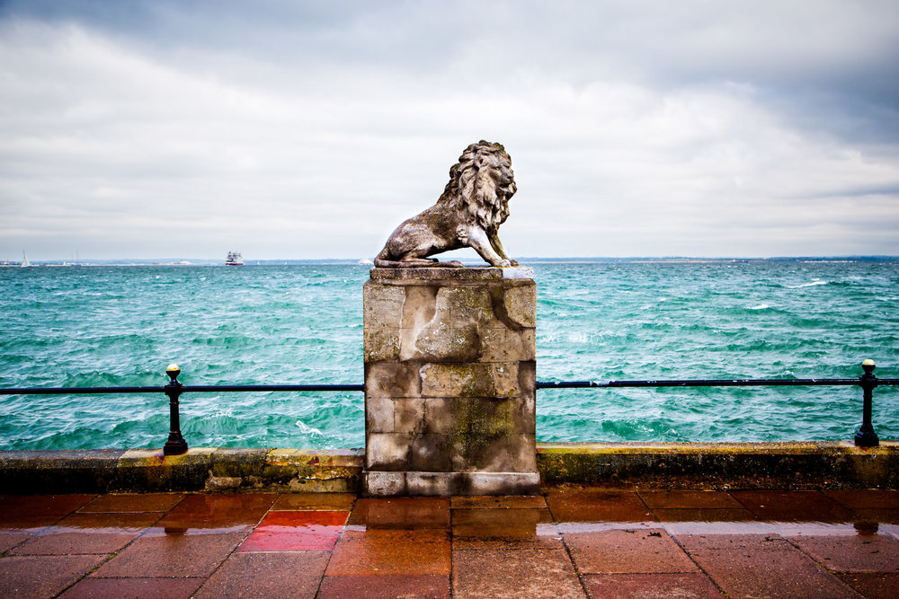 A statue of a lion set against the distant background of the UK mainland.