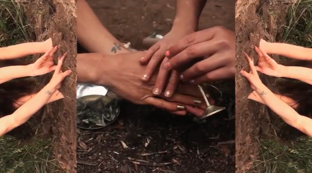 Weaving hands and earth in ritual on Ohlone land. From the film: Release from Identity Control by Rebekah Erev & Wu Li Leung