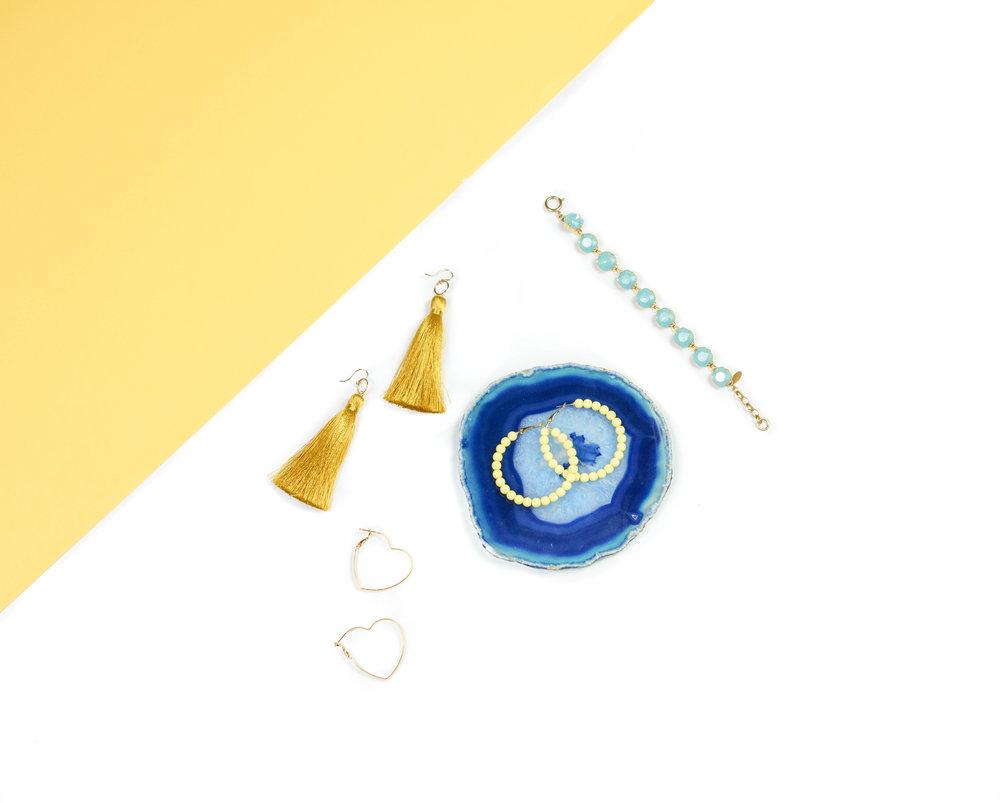 Golden Silk Tassel Earrings, $45. Yellow Beaded Hoop Earrings, $18. Gold Heart Hoop Earrings, $41. Blue Crystal La Vie Bracelet, $115.